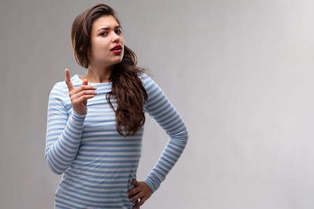 Young dogmatic woman having a serious discussion wagging her finger to make a point as she looks sideways at the camera over a grey studio background with copy space