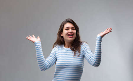 Happy joyful young woman gesturing with her hands and laughing over a grey studio background