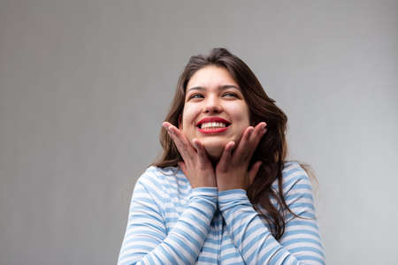 Happy young woman filled with hope and a positive attitude looking up with a joyful smile and hands to her cheeks over a grey studio background Reklamní fotografie