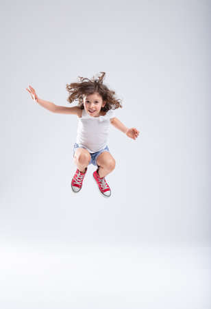 Energetic little girl jumping high into the air with bent knees and a happy smile in her red sneakers over a white background with copy space