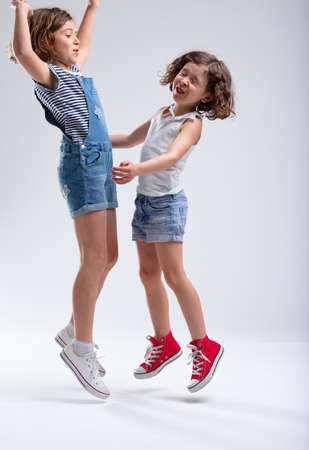 Two young sisters jumping and laughing together in blue denim shorts as they enjoy their summer vacation over a white background