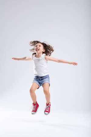 Fröhliches, energisches, aktives kleines Mädchen in Denim-Shorts und roten Turnschuhen, das mit ausgestreckten Armen über einem weißen Hintergrund mit Kopierraum hoch in die Luft springt