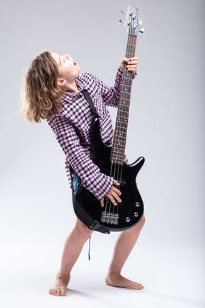 Young hipster barefoot girl playing electric guitar and singing an accompanying lyric during a live performance or practice as she follows her passion for music, full length on grey Stock Photo