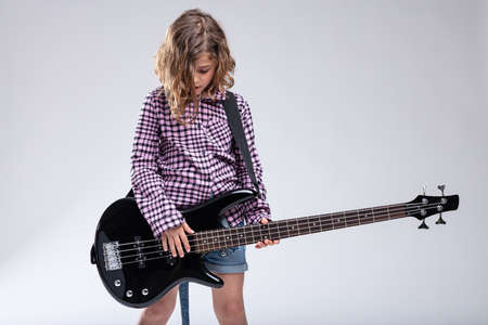 Gifted young girl progeny playing an electric guitar with downcast head absorbed in the music over a grey studio background