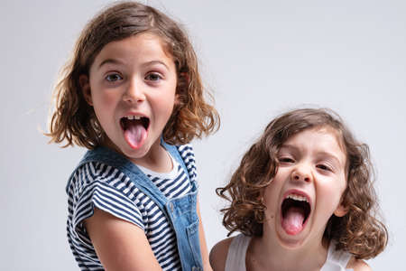Playful little girls sticking out their tongues at the camera as they stand stand by side on a white background