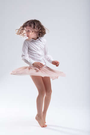 Cute little barefoot girl doing a pirouette over a white studio background with her pink tutu or skirt flying out round her as she turns