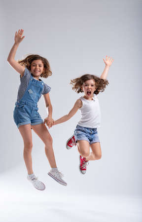 Exuberant young sisters jumping for joy high into the air holding hands and laughing at the camera over a white background with copy space