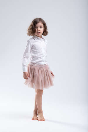 Little girl in pink ballet tutu or filmy skirt standing ready with her bare feet crossed to perform a pirouette over a white studio background