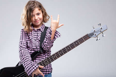 Smiling young girl playing guitar giving a horns sign gesture with her hand for rock and heavy metal music over a grey background with copy space Stock Photo