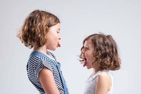 Mischievous naughty little sisters sticking out their tongues at each other as they face off in a side view portrait isolated on white