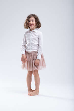 Cute little barefoot girl standing pigeon toed crossing her bare feet in a filmy pink skirt while grinning merrily at the camera isolated on white
