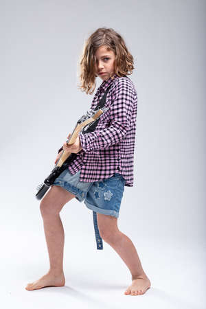 Gifted young barefoot schoolgirl playing electric guitar with a serious determined expression as she follows her passion for music in a full length portrait on grey Stock Photo
