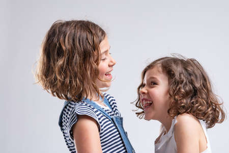 Two cheerful pretty little sisters giggling and laughing together in a close up side view portrait on white Stockfoto