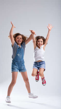 Two exuberant hyperactive young girls jumping for joy with raised arms and beaming smiles of pleasure over a white background Stockfoto