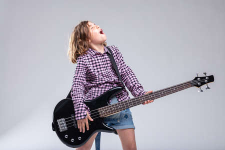 Talented young girl guitarist playing electric guitar singing a lyric to accompany her music during a live performance over a grey studio background with copy space