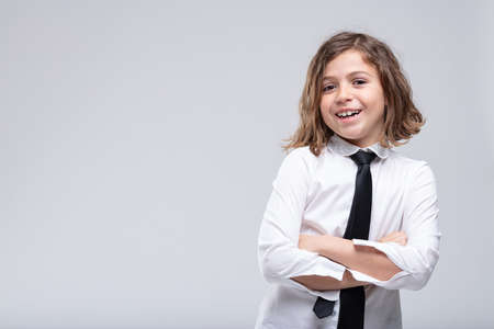 Happy young schoolgirl with a lovely friendly smile posing with folded arms over a white background with copy space