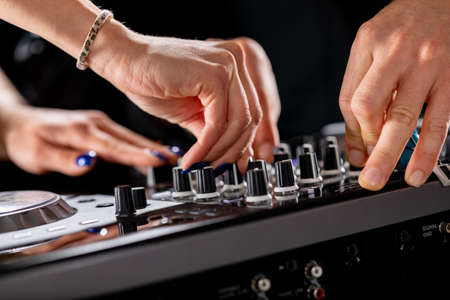 male and female DJ hands on a DJ console