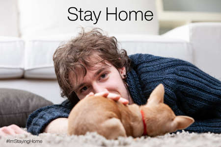 young man staying at home in a living room playing with his puppy far away from  virus COVID19 infection out there