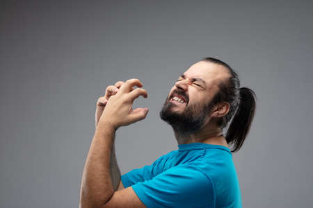 Bearded man with combed black hair showing grimace of pain with his both hands up in front of his face in squeezing gesture. Side portrait against grey background Stock Photo