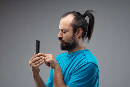 Bearded man in blue t-shirt and with black hair combed in ponytail using smartphone, holding it up close to his face, and poking on the screen. Studio side portrait isolated on grey background