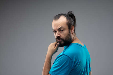 Bearded man with black hair combed in ponytail, standing in blue t-shirt against grey background and looking back at camera with a finger to his chin and calm questioning face. Copy space