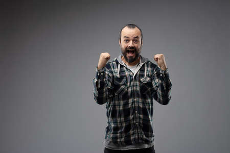 Bearded man in checked shirt showing happiness and excitement with winning gesture, celebrating success. Front half-length portrait against grey background with copy space