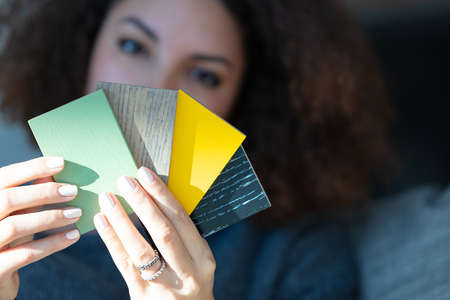 A close up of a young woman holding multiple paint palette or cladding samples. 写真素材