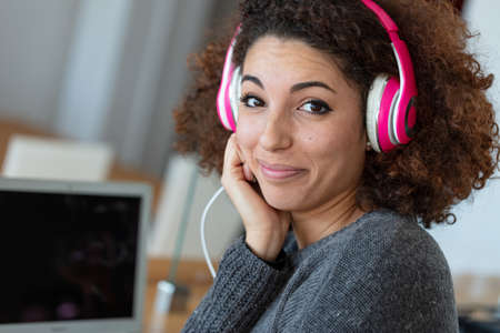 A happy, young woman with frizzy hair wearing headphones while working on a laptop from home.