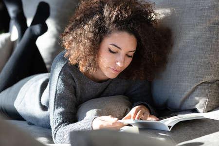 A pretty young woman lying on a modern lounge reading a magazine. Фото со стока