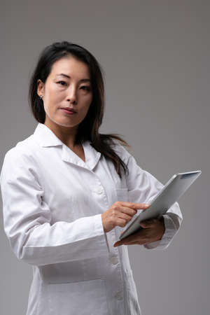 Female Asian doctor looking quizzically at the camera as she holds a clipboard in her hand pointing to the notes over grey