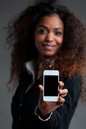 Smiling friendly woman holding out a mobile phone extended to the camera with a blank screen and focus to the cellphone