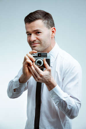 Smiling handsome young man in white shirt and black necktie looking forward while taking a picture with vintage photo camera