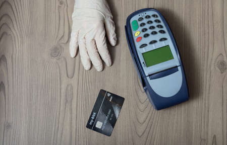 Hand in a protective disposable glove with bank card and banking machine on a wooden shop counter conceptual of shopping during the Covid-19 pandemic