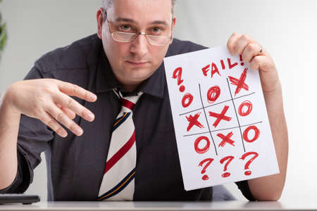 Despondent man holding up a failed tic-tac-toe or noughts and crosses game showing the hand drawn grid with no winner and question marks and text - Fail - in a concept of failure or being unsuccessful