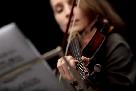 Woman playing a classical violin during a recital in a close up cropped low angle with focus to her fingers on the strings