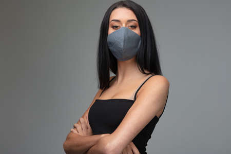 Confident attractive woman wearing a stylish fashionable protective face mask posing with folded arms on grey in a concept of adapting to post coronavirus fashion and lifestyle