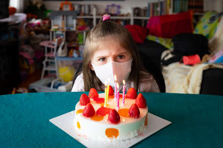 Young girl wearing a face mask during the Covid-19 or coronavirus pandemic on her birthday sitting at a table frowning as she tries to work out how to blow out the burning candles on her cake but she's sad because she can't because of that annoying mask 免版税图像