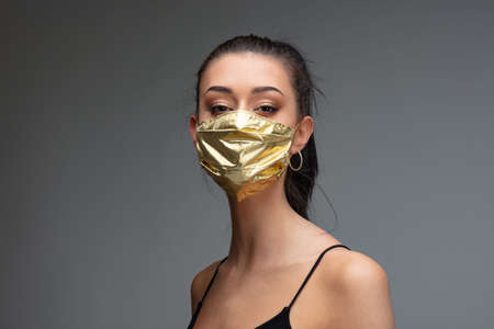 haughty woman wearing a golden face mask - concept of surgical masks price rise when they are mandatory and as extremely rare as they are needed to mitigate the COVID19 virus pandemic spread