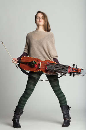 Proud young woman holding a modern reproduction of the traditional Swedish medieval nyckelharpa in a full length portrait over grey