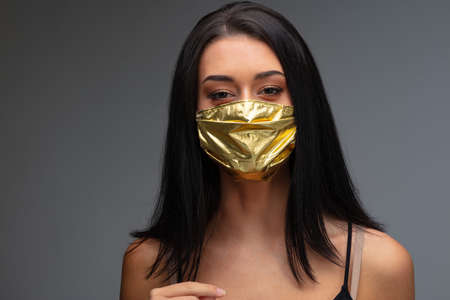 price rise of face masks and scarcity in COVID-19 times concept as a beautiful young woman wearing a face mask made of gold because she can afford it even if they are become an extremely rare good Stock Photo