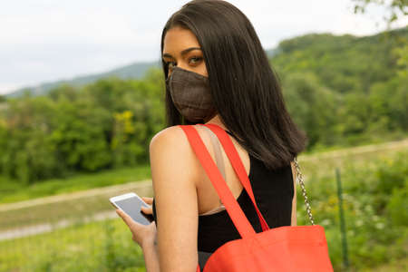Young woman wearing a black face mask as protection against the spread of coronavirus walking outdoors with her mobile phone looking back at camera