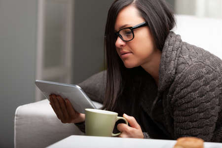 woman reading or watching videos on her digital tablet at home on her sofa while having a warm drink Stok Fotoğraf