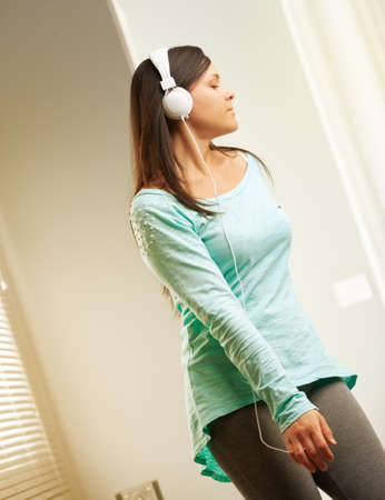 young long haired woman with headphones dancing in her living room