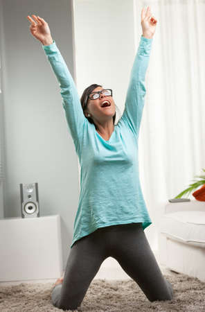 woman feeling successful for some  winning reason in her house, precisely in her living room