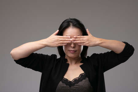 Asian woman in a smart black outfit covering her yes with her hands in a concept of the metaphor see no evil, hear no evil speak no evil, over a grey studio background Banco de Imagens