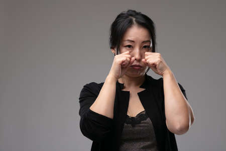 Sorrowful sad Asian woman crying raising her hands to her tearful face over a grey studio background with copyspace Stock Photo