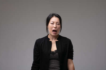 Woebegone Asian woman crying and wailing in her grief or bereavement over a grey studio background with copyspace