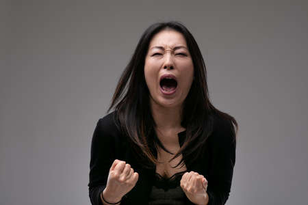 Agitated upset woman yelling in anguish or frustration with clenched fists over a grey studio background with copyspace