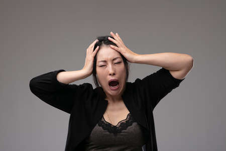Woeful Asian woman holding her head in anguish as she cries and laments over a grey studio background with copyspace