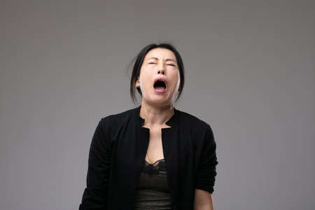 Woeful Asian woman wailing in anguish with her mouth open and a sorrowful expression over a grey studio background with copyspace